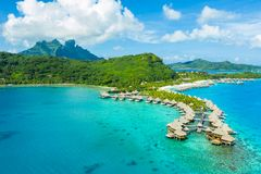 Travel vacation paradise aerial image with overwater bungalows in coral reef sea. Travel vacation paradise aerial drone video with overwater bungalows luxury stock image