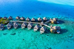 Travel vacation paradise aerial image with overwater bungalows in coral reef sea. Travel vacation paradise aerial drone video with overwater bungalows in coral stock images