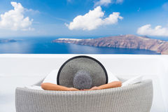 Travel vacation woman relaxing enjoying Santorini. Looking at famous view of Caldera. Young lady lying down on sun bed sofa lounge chair on holidays. Amazing royalty free stock photography