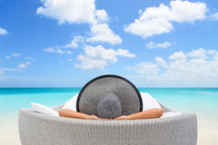Travel vacation woman relaxing lying down. On sun bed sofa lounge chair on holidays. Sleeping person lounging in hat on outdoor beach daybed lounger on ocean stock photo