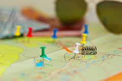 Travel in van concept. Traveling by van or bus concept - tiny bus stands on the map. Travel route is marked by pins. Passport with cash and sunglasses lie nearby Royalty Free Stock Photos