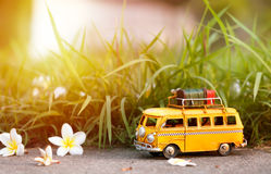 Travel van. Miniature yellow van with jungle grass summer scene Royalty Free Stock Images