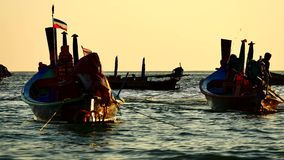 Silhouette long tail boat floating in the andaman sea with the boat was sailing through and golden light. Travel Video silhouette long tail boat converted to stock footage