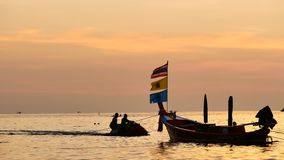 Silhouette boat excursions floating in the andaman sea with golden light. Travel Video silhouette long tail boat converted to boat excursions floating in the stock video footage
