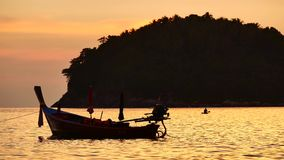 Silhouette boat excursions floating in the andaman sea with golden light. Travel Video silhouette long tail boat converted to boat excursions floating in the stock video