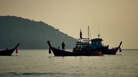 Travel video silhouette Long-tail boats sailing on the andaman. Sea with golden light of the Sun before sunset in travel or transportation concept stock video footage