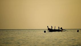 Travel video silhouette Long-tail boats sailing on the andaman. Sea with golden light of the Sun before sunset in travel or transportation concept stock footage