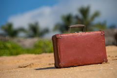 Travel  vintage suitcase is alone on a beach Stock Photos