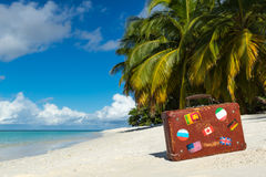 Travel  vintage suitcase is alone on a beach.  Stock Photo