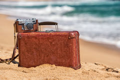 Travel  vintage suitcase and camera on a beach.  Stock Photo