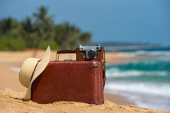Travel  vintage suitcase and camera on a beach Stock Photography