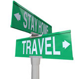 Travel Vs Stay Home Words Two Way Street Road Intersection Signs. Travel and Stay Home words on green two way road intersection signs as choices to leave for Royalty Free Stock Image