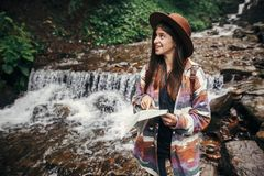 Travel and wanderlust concept. stylish hipster girl in hat with. Backpack exploring map, standing at river with waterfall in mountains. traveler woman traveling Royalty Free Stock Image