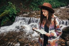 Travel and wanderlust concept. stylish hipster girl in hat with. Backpack exploring map, standing at river with waterfall in mountains. traveler woman traveling Royalty Free Stock Images