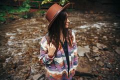 Travel and wanderlust concept. stylish hipster girl in hat with. Backpack relaxing in forest in mountains. traveler woman exploring summer woods. atmospheric Stock Image