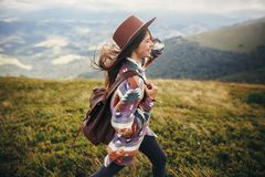 Travel and wanderlust concept. stylish traveler hipster girl holding hat, with backpack and windy hair, walking in mountains in c. Louds. summer vacation. space royalty free stock photos