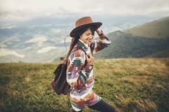 travel and wanderlust concept. stylish traveler hipster girl holding hat, with backpack and windy hair, walking in mountains in c royalty free stock image