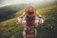 Travel and wanderlust concept. stylish traveler hipster girl hol. Ding hat, with backpack and windy hair, walking in mountains in clouds. summer vacation. space royalty free stock image