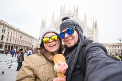 Travel in winter concept - Young and happy tourist making selfie photo in front of the famous Duomo cathedral in Milan. Happy vacations in Milan royalty free stock photos