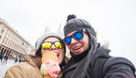 Travel in winter and Italy concept - Happy young couple take selfie photo with ice-cream in front of Milan Duomo. Cathedral stock images