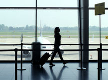 Travel woman in airport. Woman carrying luggage in the airport departure gate preparing to travel by plane stock photos