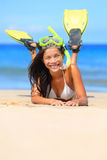 Travel woman on beach vacation with snorkel. Lying in sand with snorkeling mask and fins smiling happy enjoying the sun on sunny summer day. Multi ethnic Asian Royalty Free Stock Photography