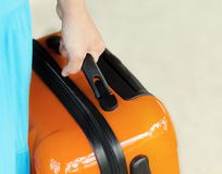 Woman in blue dress holds orange suitcase Stock Images