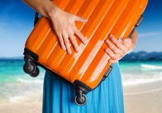 Woman in blue dress holds orange suitcase Royalty Free Stock Photography