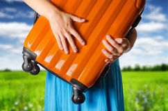 Woman in blue dress holds orange suitcase Royalty Free Stock Photo