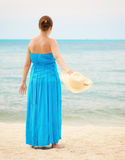 Woman in blue dress throws hat on the beach Stock Images