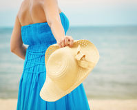 Woman in blue dress throws hat on the beach Stock Image