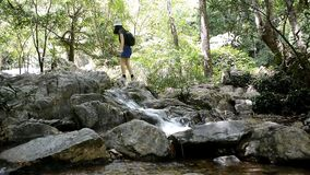 Travel woman climbing rocks to waterfall stock video