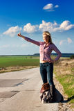 Travel  woman hitchhiking. Pretty young Travel  woman hitchhiking along an empty  country road with sun shinning in her face Stock Photos