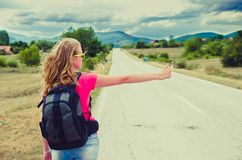 Travel woman hitchhiking. Travel concept. Travel woman hitchhiking on the mountain road Royalty Free Stock Photography