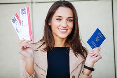 Travel. Woman holding two air ticket in abroad passport near airport royalty free stock photos