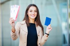 Travel. Woman holding two air ticket in abroad passport near airport stock image