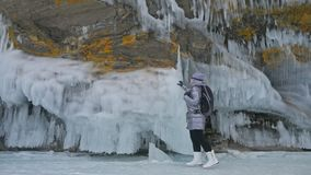 Travel of woman on ice of Lake Baikal. Trip to winter island. Girl is walking at foot of ice rocks. Traveler looks at. Beautiful ice grotto. Hiker wears sports stock video