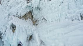 Travel of woman on ice of Lake Baikal. Trip to winter island. Girl is walking at foot of ice rocks. Traveler looks at. Beautiful ice grotto. Hiker wears sports stock footage