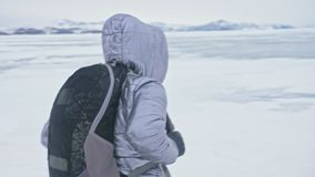 Travel of woman on ice of Lake Baikal. Trip to winter island. Girl is walking at foot of ice rocks. Traveler looks at