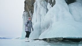 Travel of woman on ice of Lake Baikal. Trip to winter island. Girl is walking at foot of ice rocks. Traveler looks at. Beautiful ice grotto. Hiker wears sports stock video footage