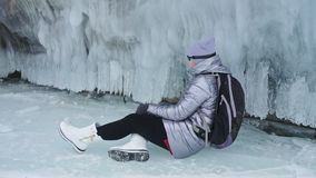Travel of woman on ice of Lake Baikal. Trip to winter island. Girl is walking at foot of ice rocks. Traveler looks at stock footage