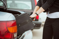 Travel: Woman Pulling Suitcase Out Of Trunk Royalty Free Stock Photography