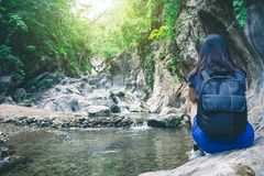 Travel woman sitting and enjoy the moment on the rock at waterfa Stock Photo