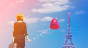 Travel woman with suitcase and balloon. Young woman in black dress with heart shape balloon and suitcase walking to Paris with Eiffel tower on background Stock Photography