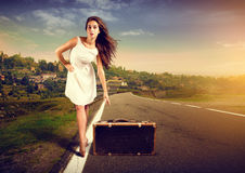 Travel. Woman traveling with suitcase at the roadside Royalty Free Stock Images