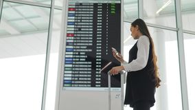 Travel woman using smartphone at airport. Young caucasian traveler checking boarding time with mobile phone app in. Travel woman using smartphone at airport stock video footage