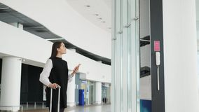 Travel woman using smartphone at airport. Young caucasian traveler checking boarding time with mobile phone app in. Travel woman using smartphone at airport stock footage