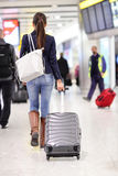 Travel Woman Walking In An Airport With Luggage Stock Photo
