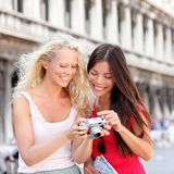 Travel - Women friends laughing having fun. Looking at picture on camera happy outside. Multiracial friends, Asian women and Caucasian blonde traveling on San Royalty Free Stock Photography