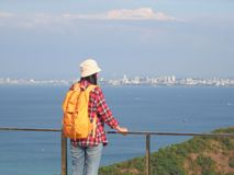Travel , Women wearing Blue jeans and red plaid shirt and backpacking yellow at viewpoint on mountain are looking at the sea.  stock photography